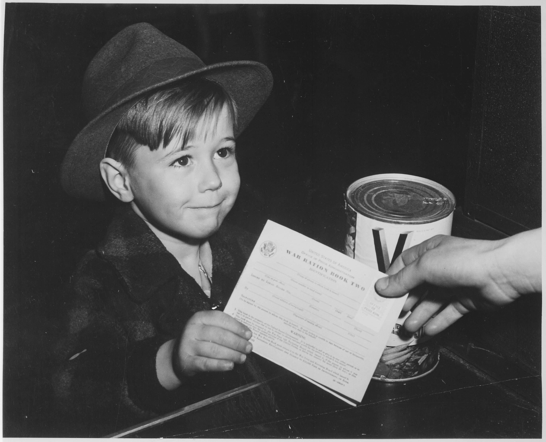 A boy turning a war ration book war school boy history