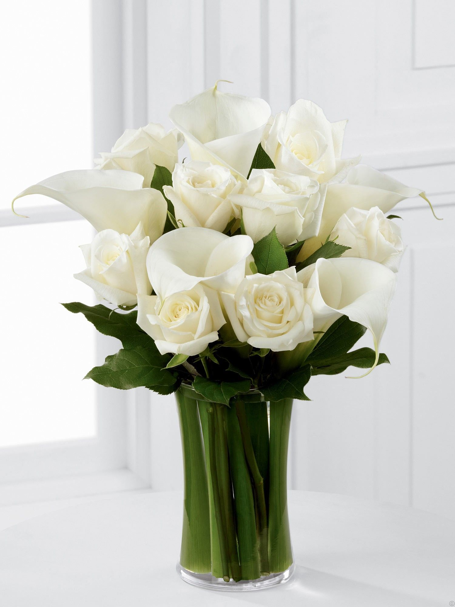 White flowers green leaves pure and clean luxury white rose luxury white rose and calla lily vase beautiful white roses and calla lilies are simply set amongst lush greens in a clear curved glass vase to create a reviewsmspy