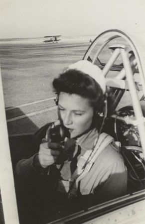 A WASP, possible Susie Winston Bain, uses the radio in the cockpit of an airplane, circa 1944 ~