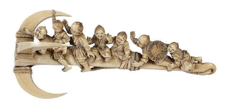 A Japanese Ivory Okimono carved as a giant anchor upon which a group of fishermen and boys are sitting in great merriment, the whole bearing a drak stain with etched details, unsigned, length 16.9cms.; with wood stand
