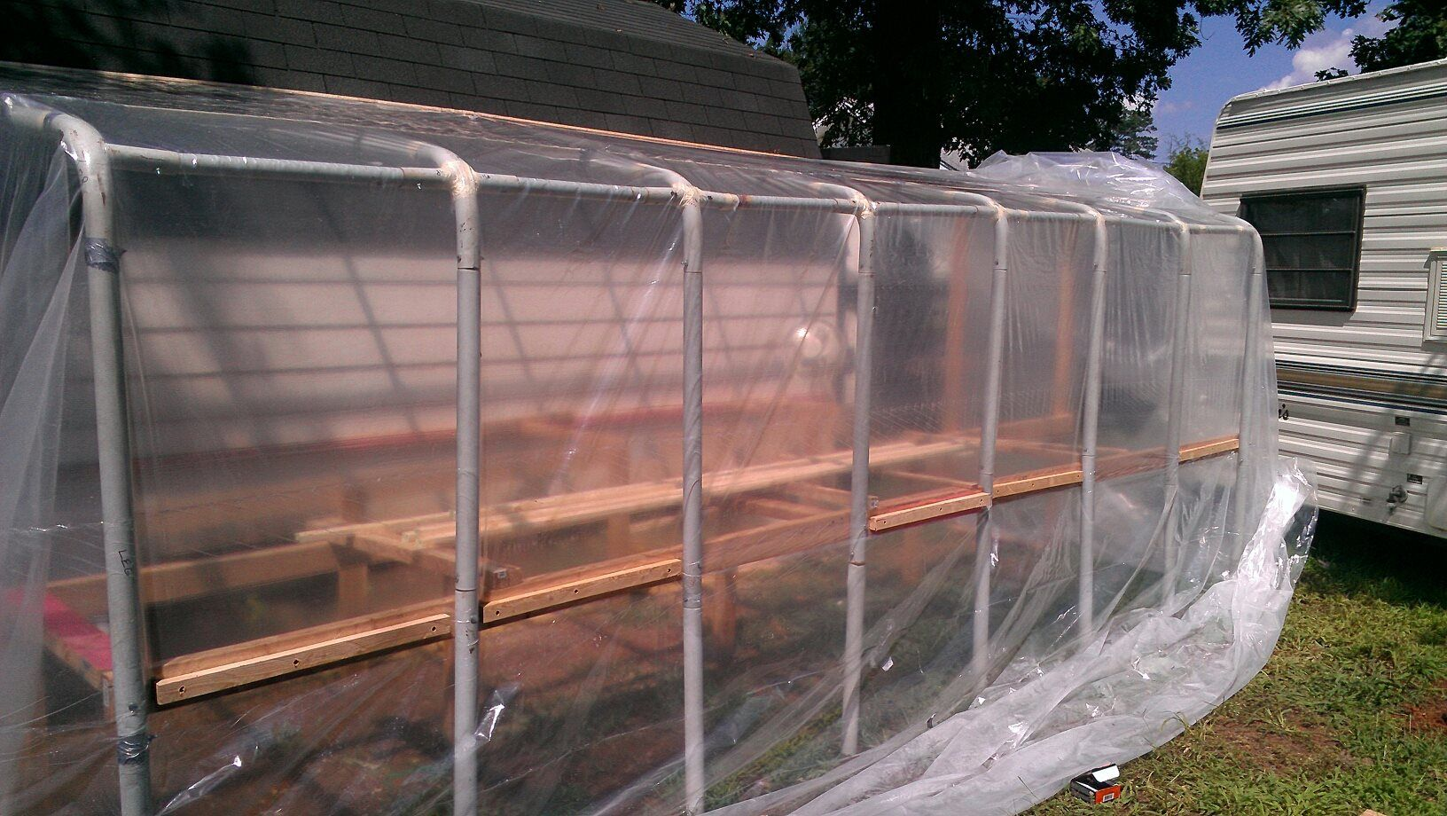 Diy greenhouse the frame was an old tent frame that was for Homemade greenhouse plastic