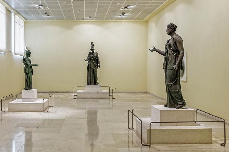 You will admire the oldest surviving cast statue in Greece, a kouros (statue of a young male) dedicated to the god Apollo, two statues of Artemis and a theatrical tragedy mask -all brass works dating from the 4th century B.C. The marble lion of Moshato, which was a funerary offering, is also exhibited here, as is the funerary monument of Nikiratos and a bronze ram 0.8 meters long from an Athenian trireme.