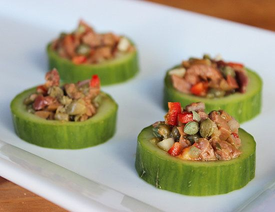 Cucumber Cups With Tapenade Recipe: 2 English cucumbers,  1/4 cup capers, rinsed,  1 1/4 c Kalamata olives, pitted, rinsed,  3 tbs finely diced red onion,  2 cloves garlic, finely minced,  1/2 small red jalapeño, or red serrano, seeded and minced,  1 tbs lemon zest,  1 tbs finely chopped oregano,  1 1/2 tbs finely chopped tarragon,  1 tbs olive oil