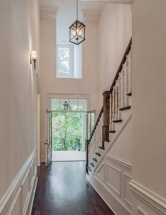 Two Story Foyer With Carriage Lantern And Dark Stained Wood Floors