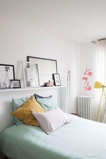 une tete de lit customisee avec des cadres et biblots