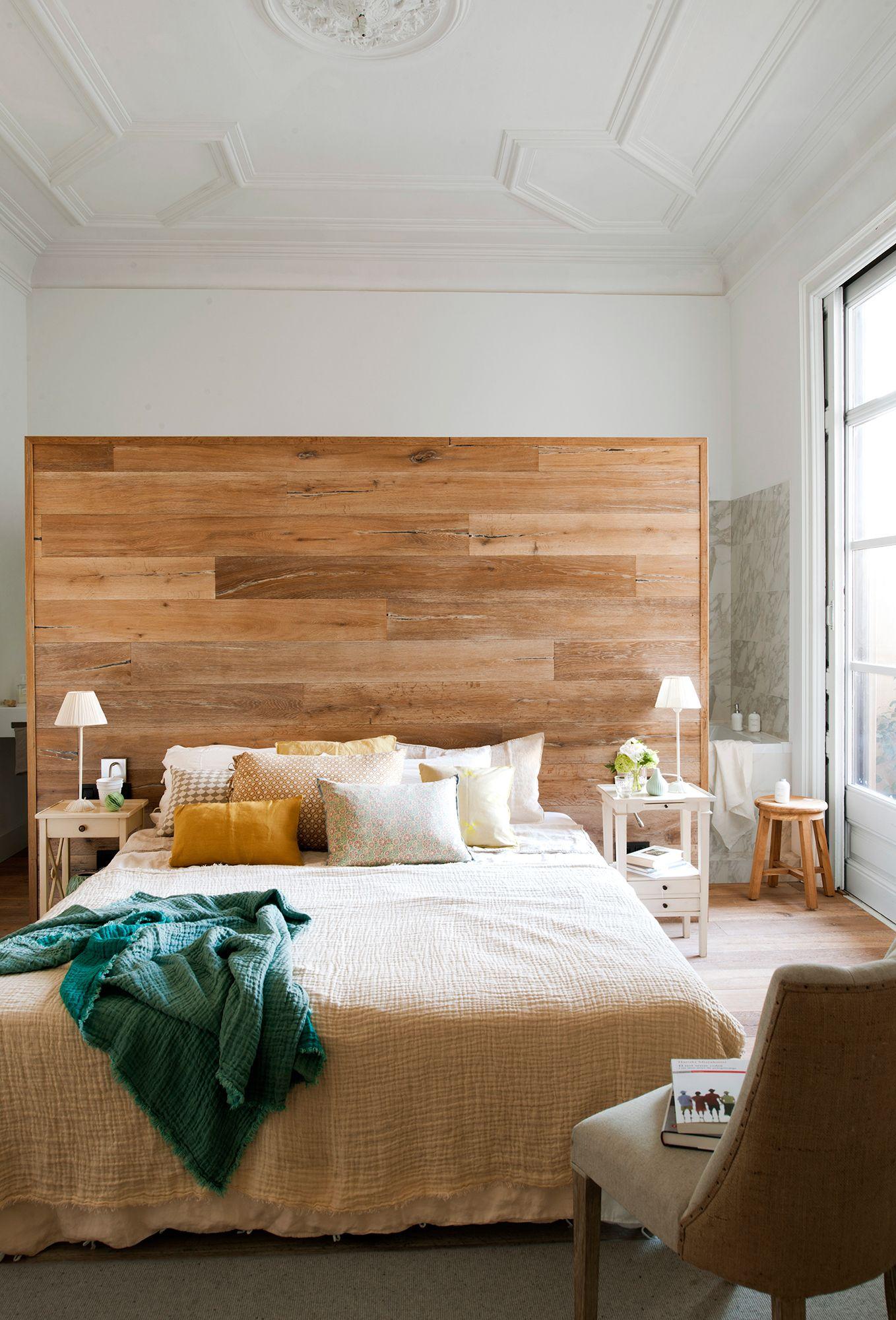 Dormitorio con murete revestido de madera y ba o tras el