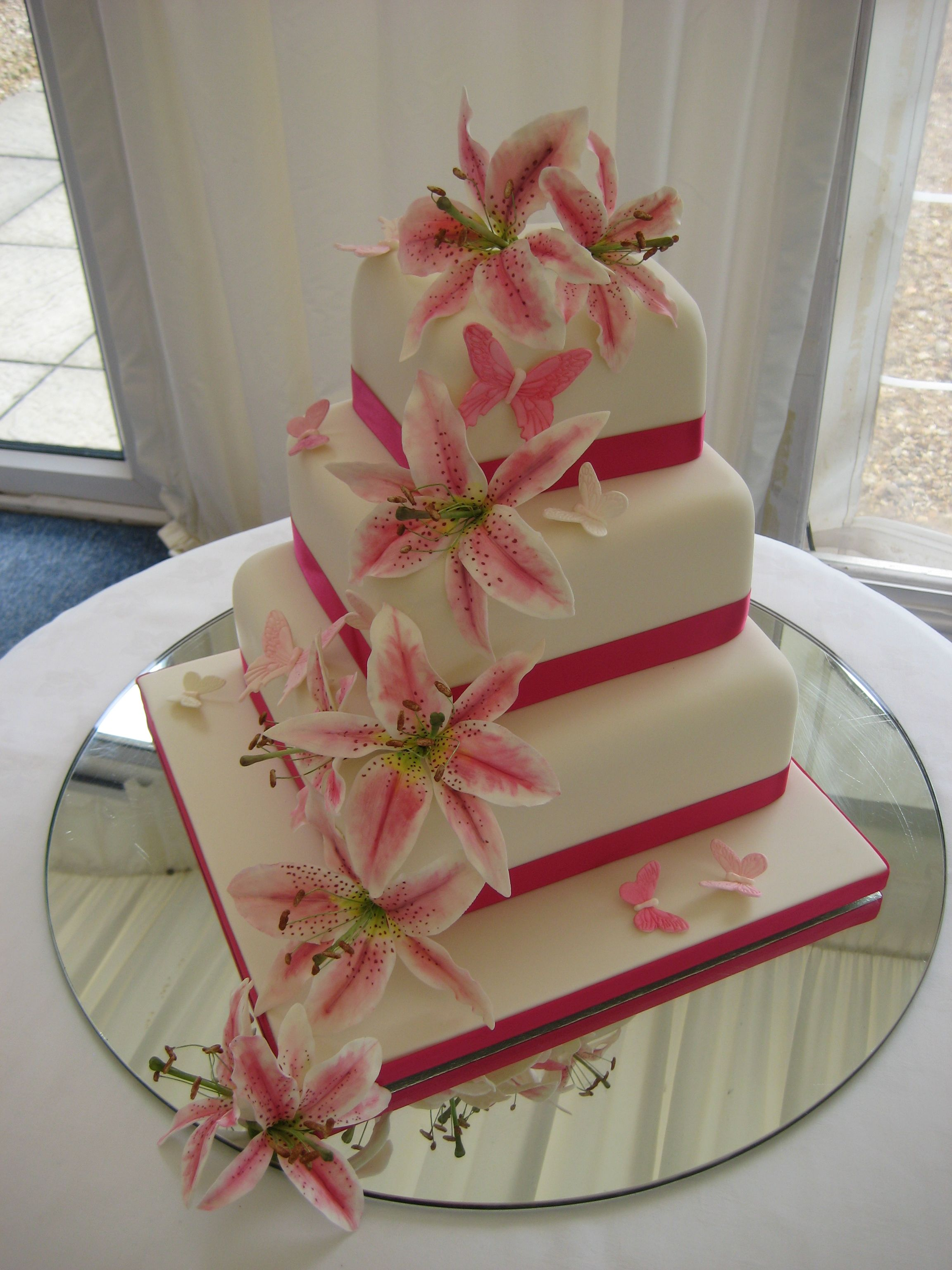 Thee tiered square wedding cake with pink sugar star gazer