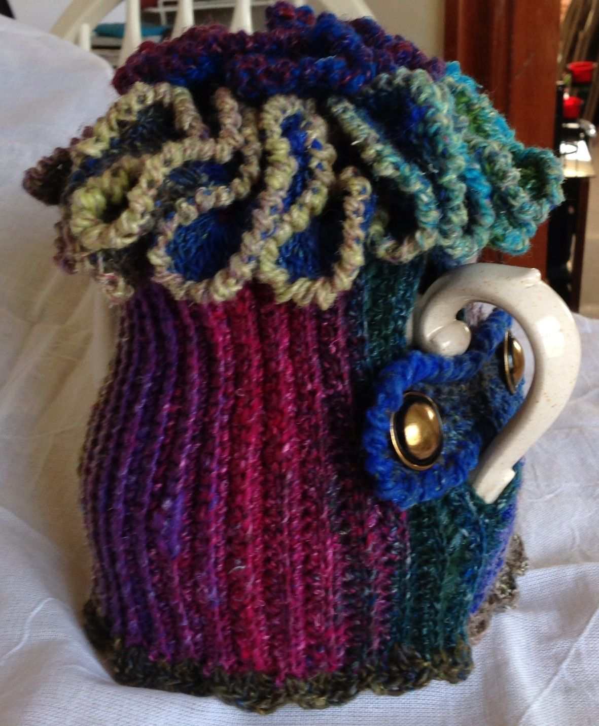 I call this my Ruffle Tea Cozy - made with Noro Silk Garden Sock and 2 vintage buttons