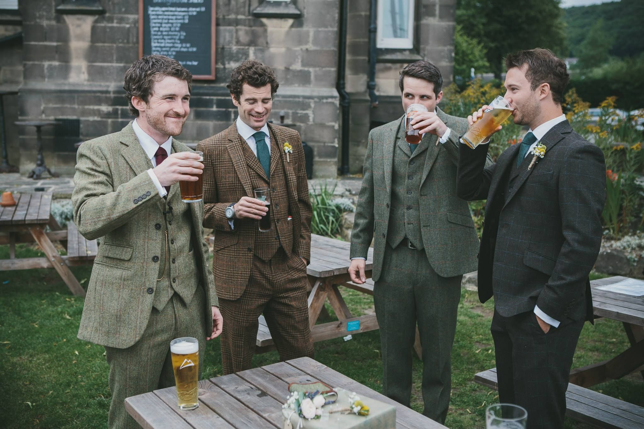 Four men after a wedding, wearing tweed suits and drinking a ...