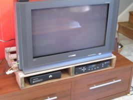 Use a pallet to store your electronic gear under your TV.