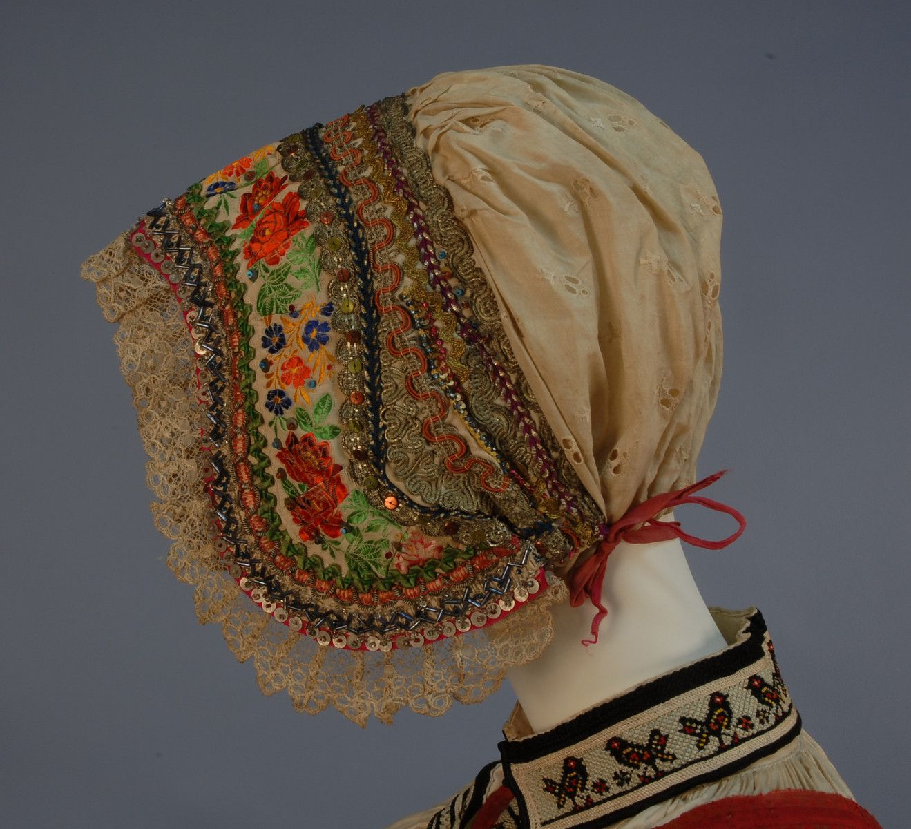 MORAVIAN KROJ or CZECH FOLK COSTUME, 19th-EARLY 20th C. Printed silk and wool skirt trimmed with red and yellow lace, navy apron with floral embroidery, tie dyed stripes and lace trim, brocaded vest in red, green, purple and yellow, embroidered blouse, three embroidered caps-two with beadwork and metallic threads, short sash.