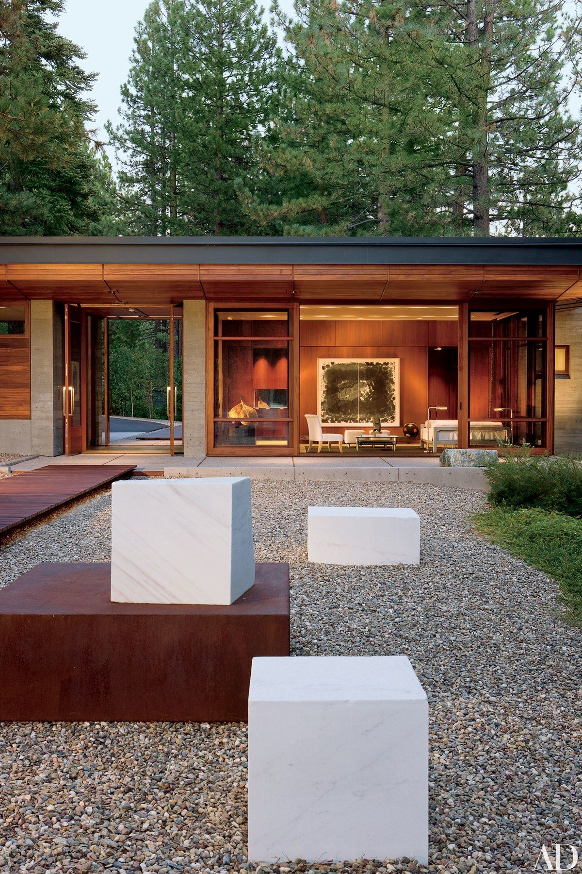 For a client's guesthouse and studio/library on the Nevada side of Lake Tahoe, architect Roderick Ashley designed two pavilions. A marble-and-steel sculpture by the project's landscape architect, Robert Murase, and his son Scott leads to the guesthouse.