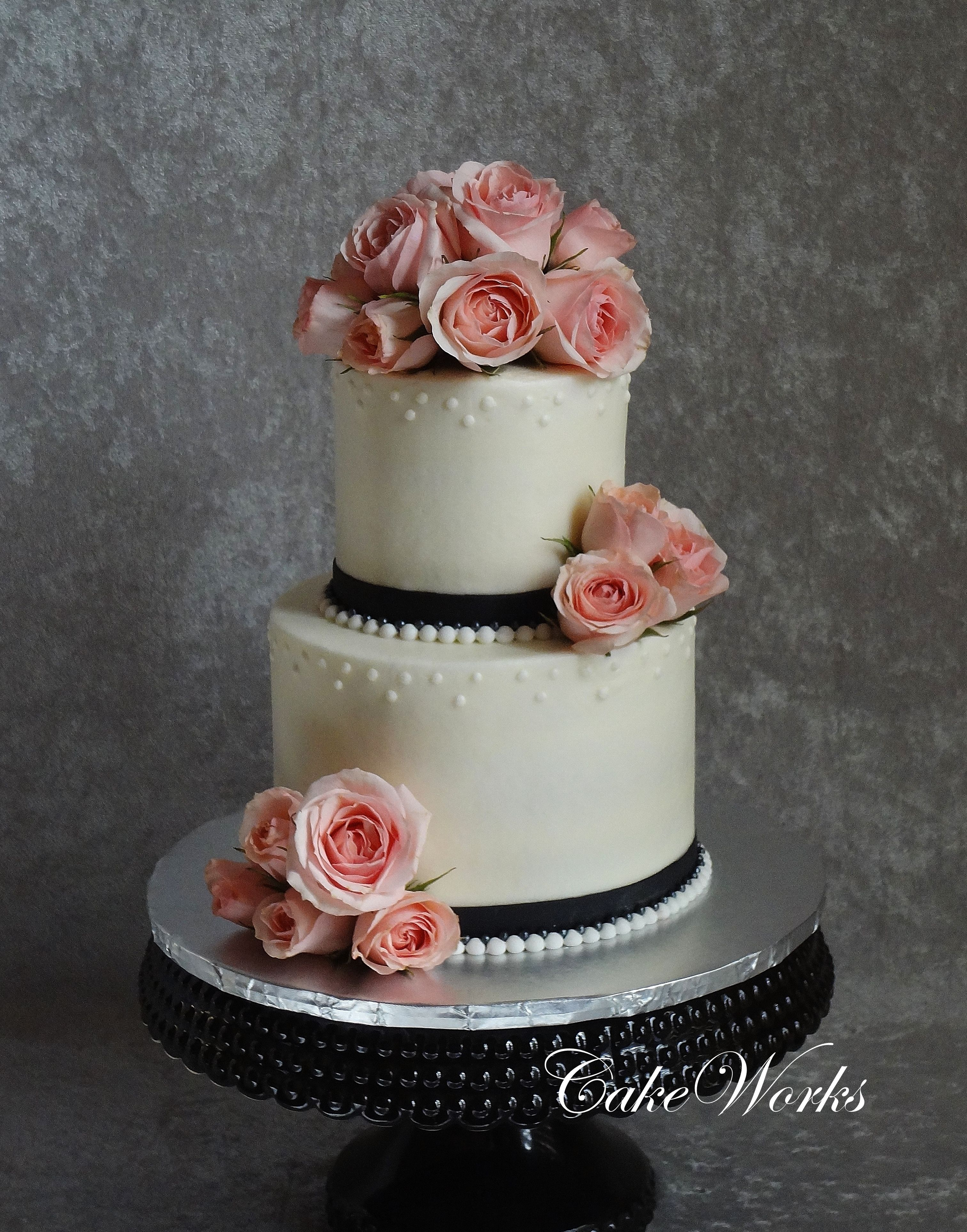 Sweetheart roses and pearls - White almond cake with raspberry cream filling iced in vanilla buttercream with black fondant ribbon and fondant pearl border.   Fresh sweetheart roses.