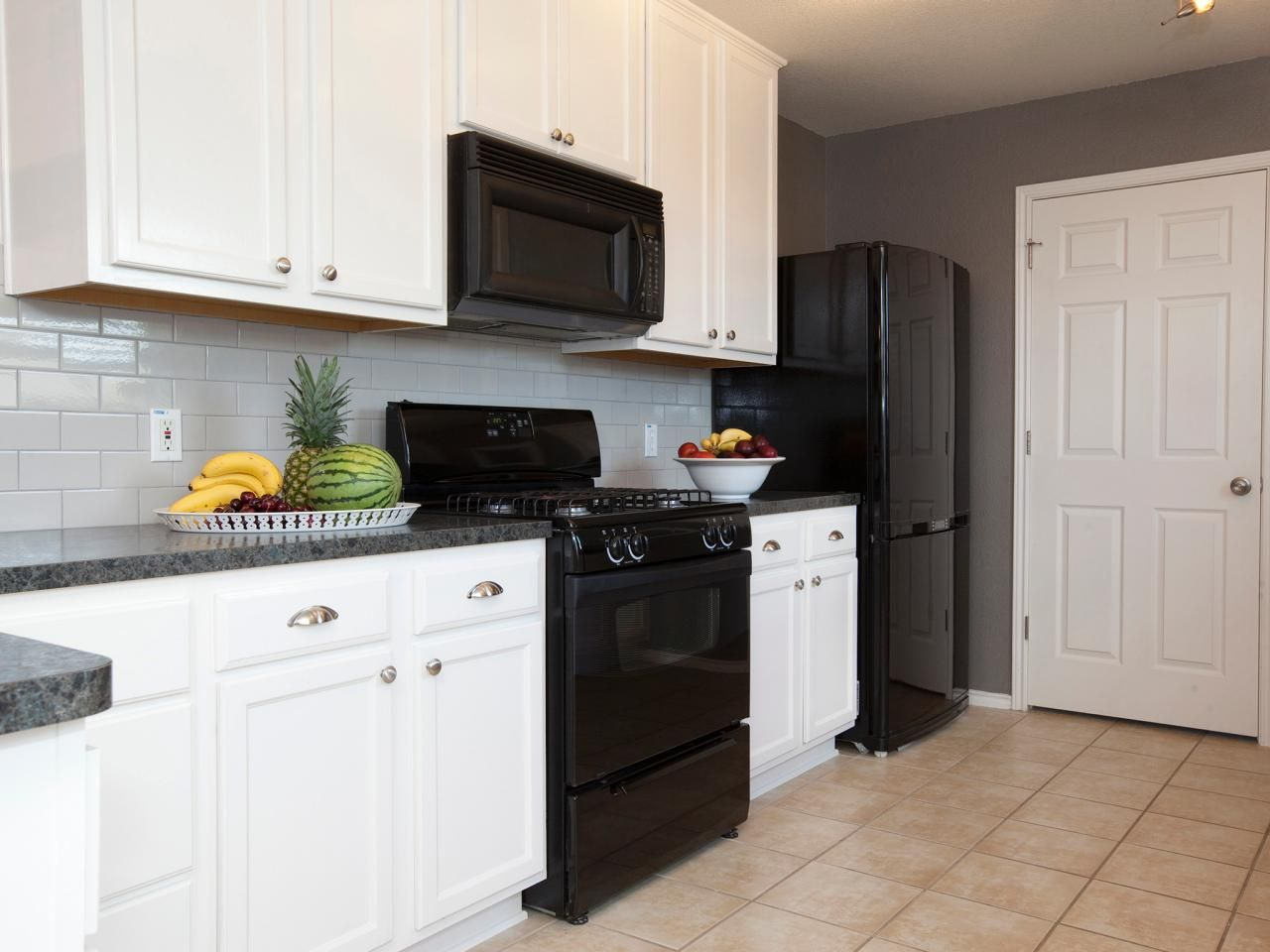 White Cabinets And Black Kitchen Appliances Pop Against The Gray Paint And Gray Su White Cabinets Black Appliances Black Appliances Kitchen Kitchen Wall Colors