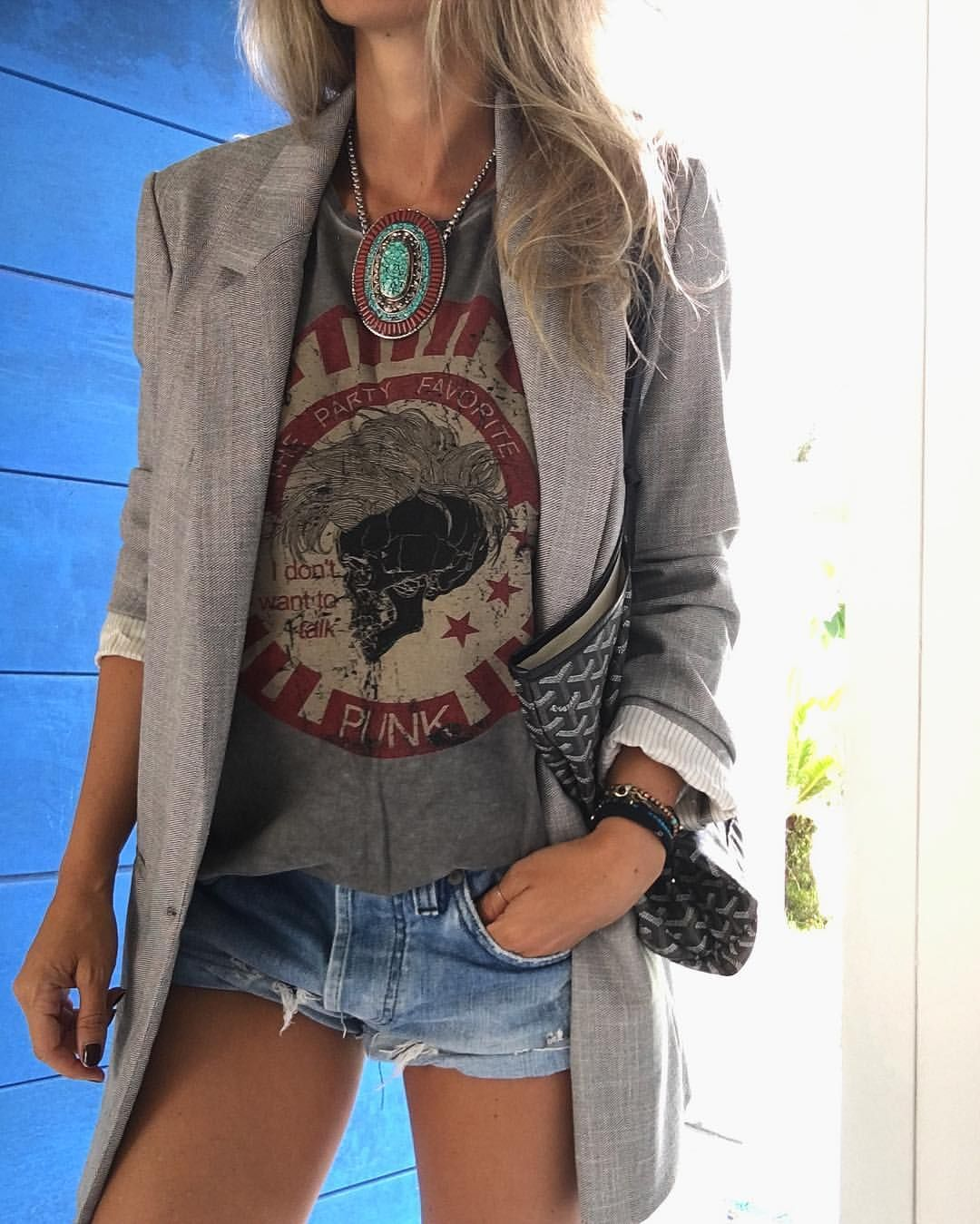An oversized blazer matched with a vintage tee & denim short shorts, and a large turquoise statement necklace.
