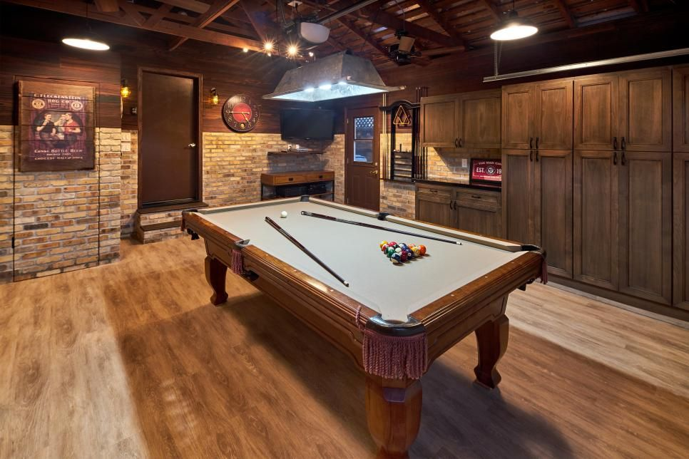 The Pool Table Sits Center Stage In The Room A Tv Is Mounted In