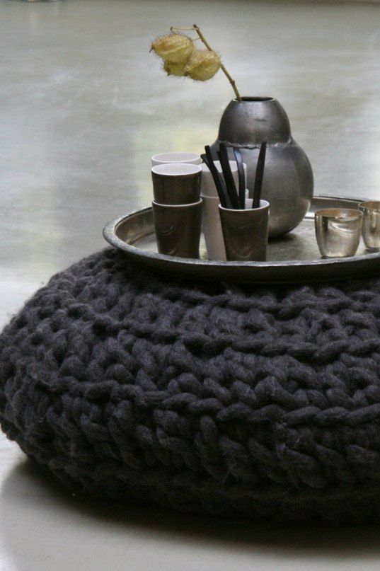 Wool ottoman. Dark charcoal colour. Concrete look flooring.  Ottoman in front of chalkboard with items on a platter sitting on top.