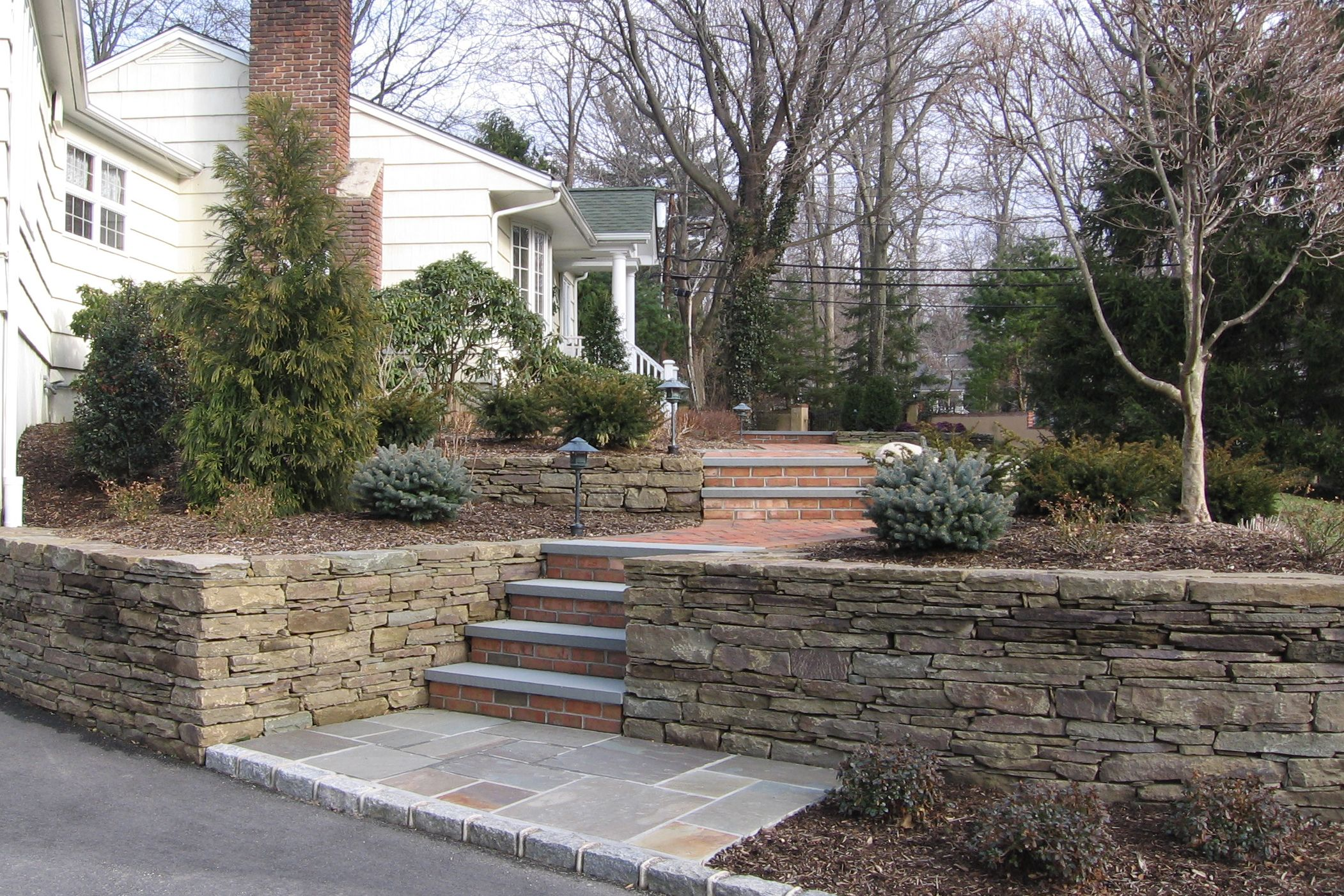 Stone Retaining Walls With Brick And Bluestone Steps Mainstreetnursery Stonewalls Retainingwalls Porch Stairs Exterior Stairs