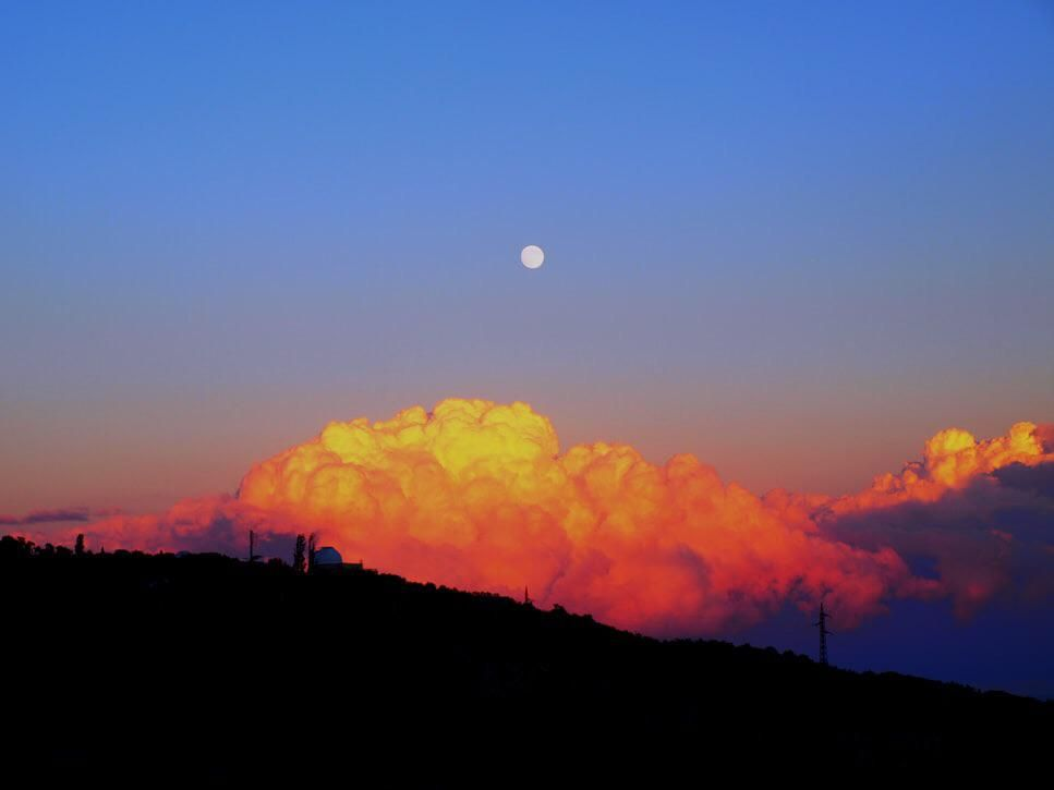 Golden clouds and full moon sunset at Crimean Peninsula