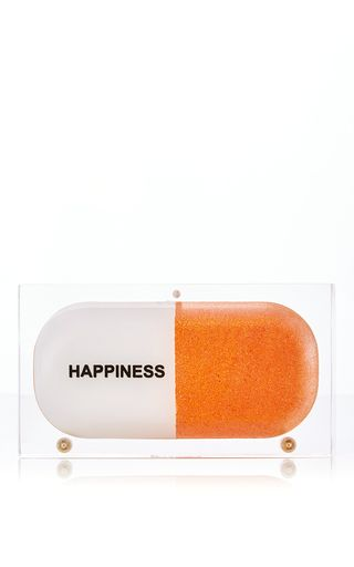 A **Sarah's Bag x Samantha Boardman** Positive Prescription collaboration, this Dr. Sam Orange Glitter Happiness Pill Clutch is hand-crafted in clear perspex and features a glitter-painted acrylic pouch inside.