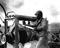 Crewman operates a winch on board USS Mockingbird (AMS-27) during mine clearance operations off Wonsan, North Korea. The ship's name is seen on a lifering mounted on the bulwark in the lower right. Original photo is dated 14 November 1950.