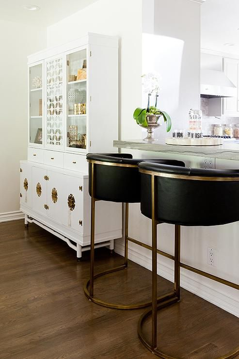 Kitchen Bar Is Lined With Black And Gold Barrel Back