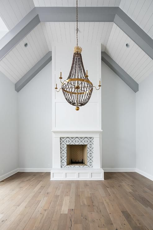 Tulum II Tiles accent a white wood fireplace mantel under a white plank vaulted ceiling and gray accent beams. #vaultedceilingdecor