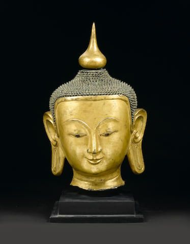 A large Burmese Shan-style gilt-lacquer head of Buddha 18th/19th century The monumental brilliantly gilded head defined by relaxed naturalistic features below an elaborately coiled and detachable usnisha. 104cm (41in) high.
