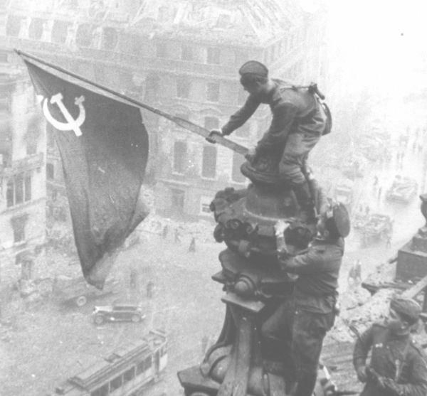 """""""Alzando una bandera sobre el Reichstag"""", tomada el 2 de mayo de 1945 por el fotógrafo Yevgeni Jaldéi en Berlín, Alemania nazi. La misma muestra a soldados del Ejército Rojo alzando la bandera de la Unión Soviética sobre el Reichstag alemán, completamente en ruinas, en la Batalla de Berlín durante el fin de la Segunda Guerra Mundial."""