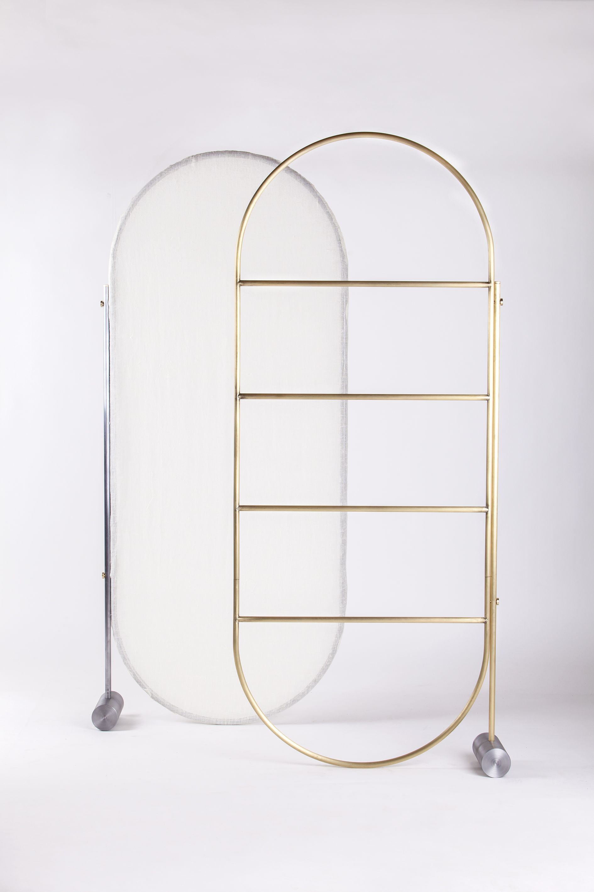 Separè (2015) by Revesz + Tatangelo is a multi-use space divider, centered around a vertical metal frame kept upright via cylindrical anchor weight at its base. A semi-transparent natural fabric covering the frame creates light and flexible division of spaces while open frame option with horizontal divisions allows for a multi-use rack.  Finishes : natural brass, natural iron.  // Manufacturer : Mingardo
