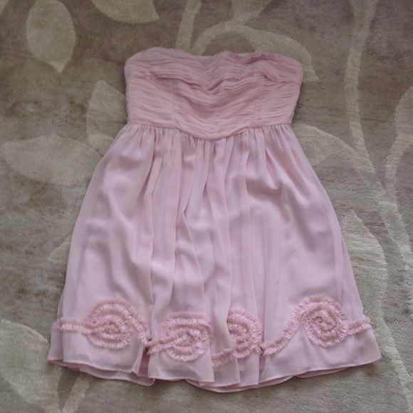 "NWOT LC Lauren Conrad Chiffon Strapless Dress Romantic chiffon dress in a soft pink hue with corset & trim detailing. Lined & with a ""rubber"" inside trim to the upper bodice in order to help it stay in place. Brand new, never been worn. LC Lauren Conrad Dresses Strapless"