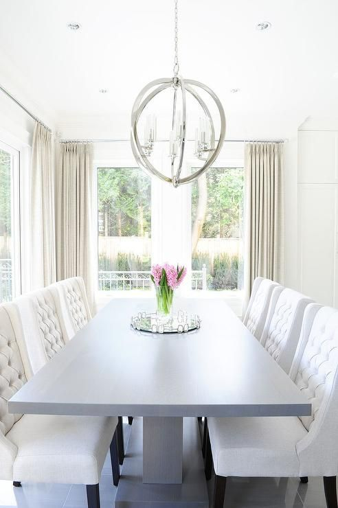 chic dining room features a gray pedestal dining table lined with
