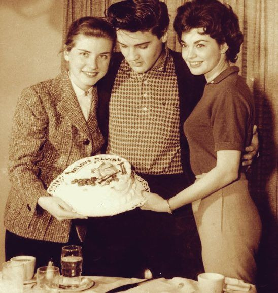 """This was a going-away party for Elvis given by the cast and crew of his fourth movie, """"King Creole"""" in Hollywood, CA on Wednesday, March 12, 1958. Twelve days later, on March 24, 1958 Elvis would be inducted into the Army. Actresses Dolores Hart (left) and Valerie Allen (right) gave Elvis that cake that was decorated with the figure of a potato-peeling, guitar-playing soldier and the words WE LOVE ELVIS."""