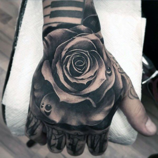 Detailed Mens Hand Tattoo Of Black Ink Rose Flower With Water Droplet Rose Hand Tattoo Hand Tattoos For Guys Black Ink Tattoos