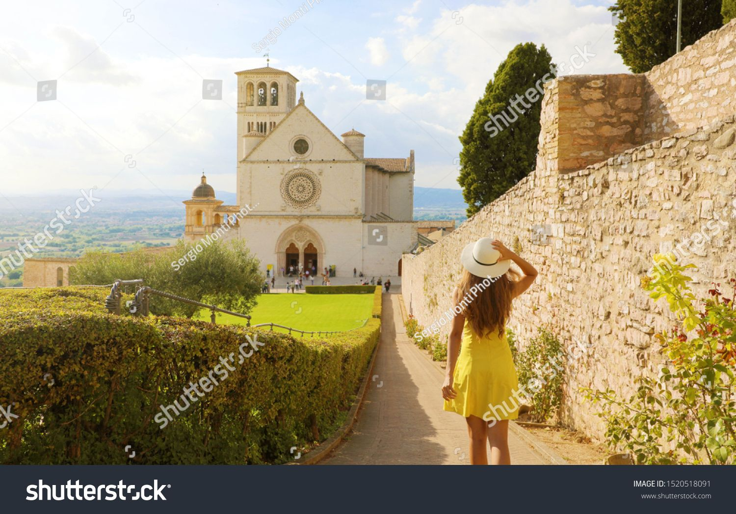 Tourism in Italy. Back view of beautiful girl walking towards the Basilica of Saint Francis of Assi