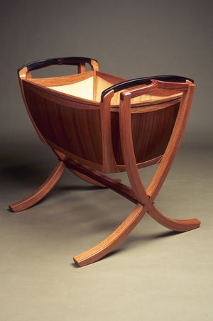 Babe's first ride handmade wooden cradle from Jarrah, Narra, Bamboo and Ebony. Functional art.