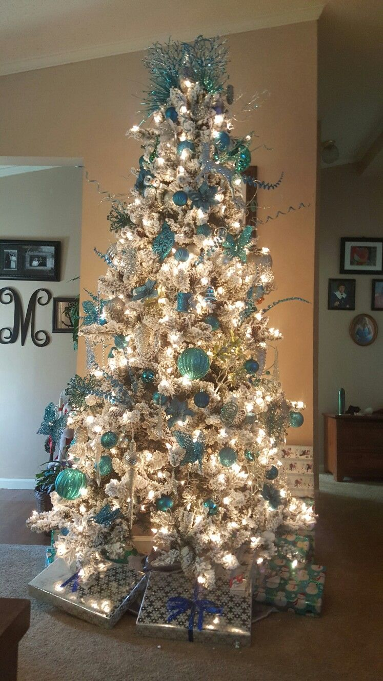 Flocked tree with teal and silver decorations. Teal