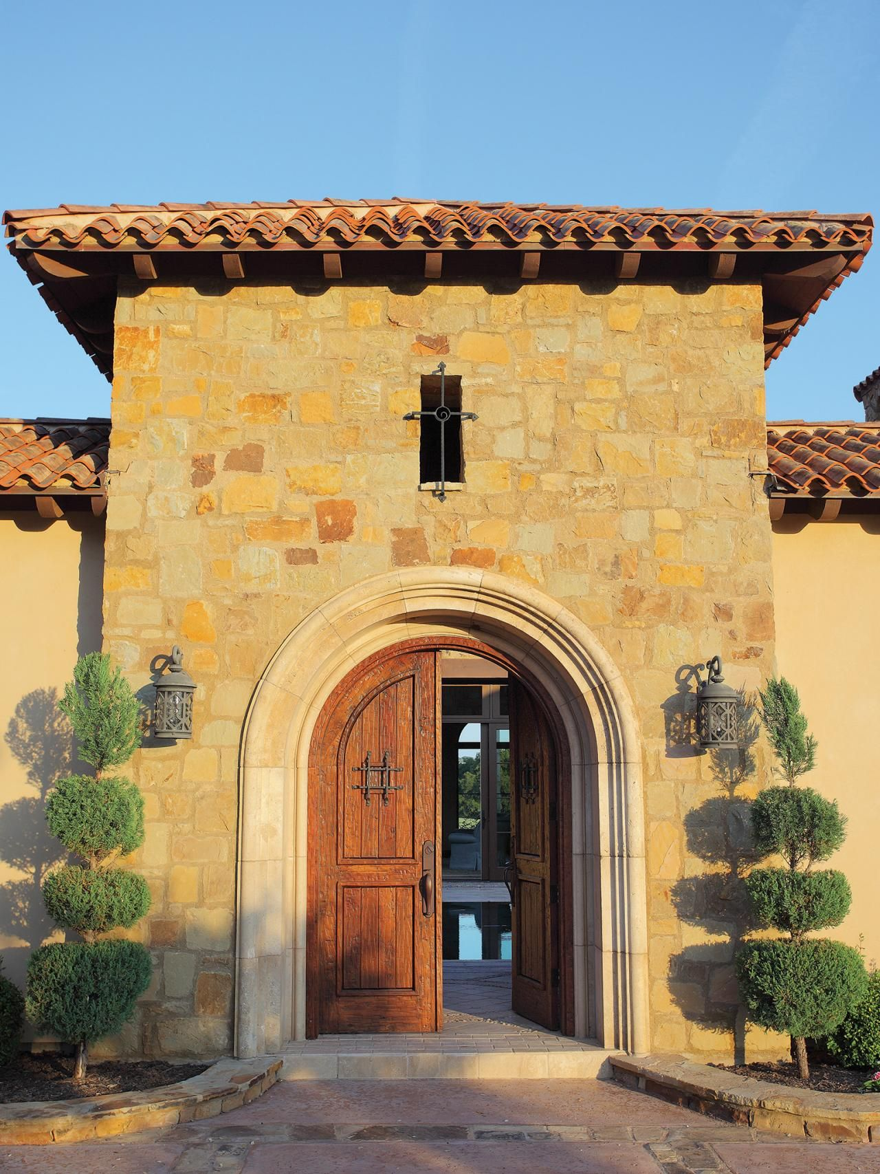 A Mediterranean home sports arched wooden front doors and a red ...