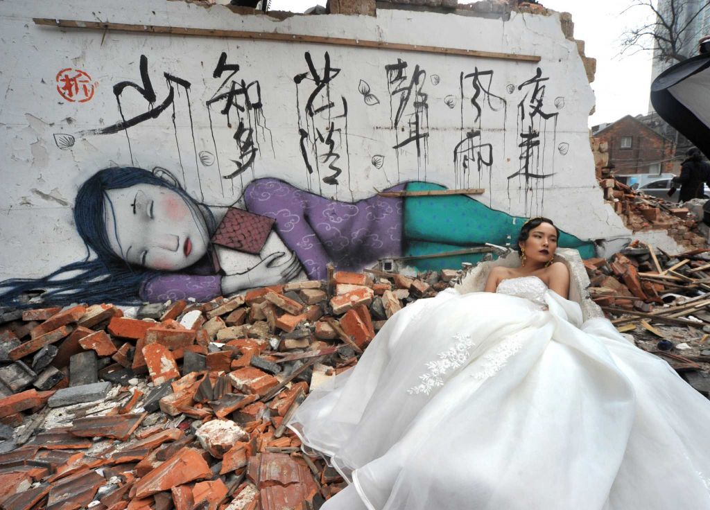 A bride poses for wedding photos at Kangding Road where old houses are demolished on January 22, 2015 in Shanghai, China. More than 10 graffiti paintings were seen on old walls which had been demolished in Jingan District in Shanghai. Photo: ChinaFotoPress, Getty Images / 2015 Getty Images