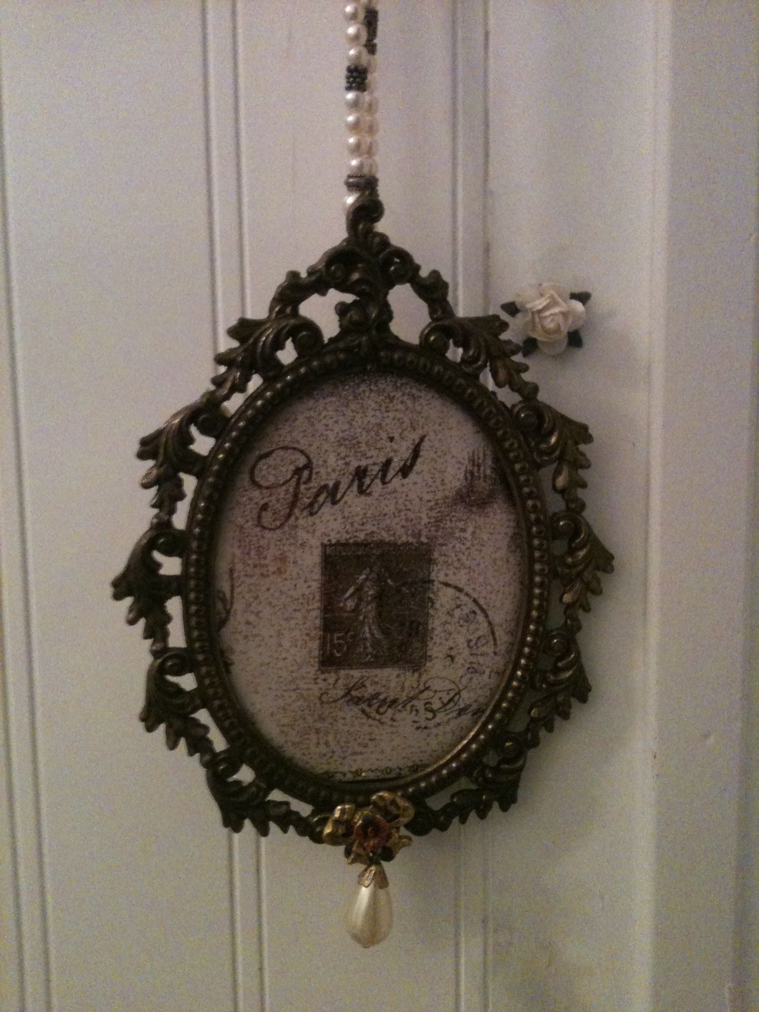 vintage metal frame, Paris wrapping paper from Hobby Lobby, glitter, and beaded pearl bracelet as hangar