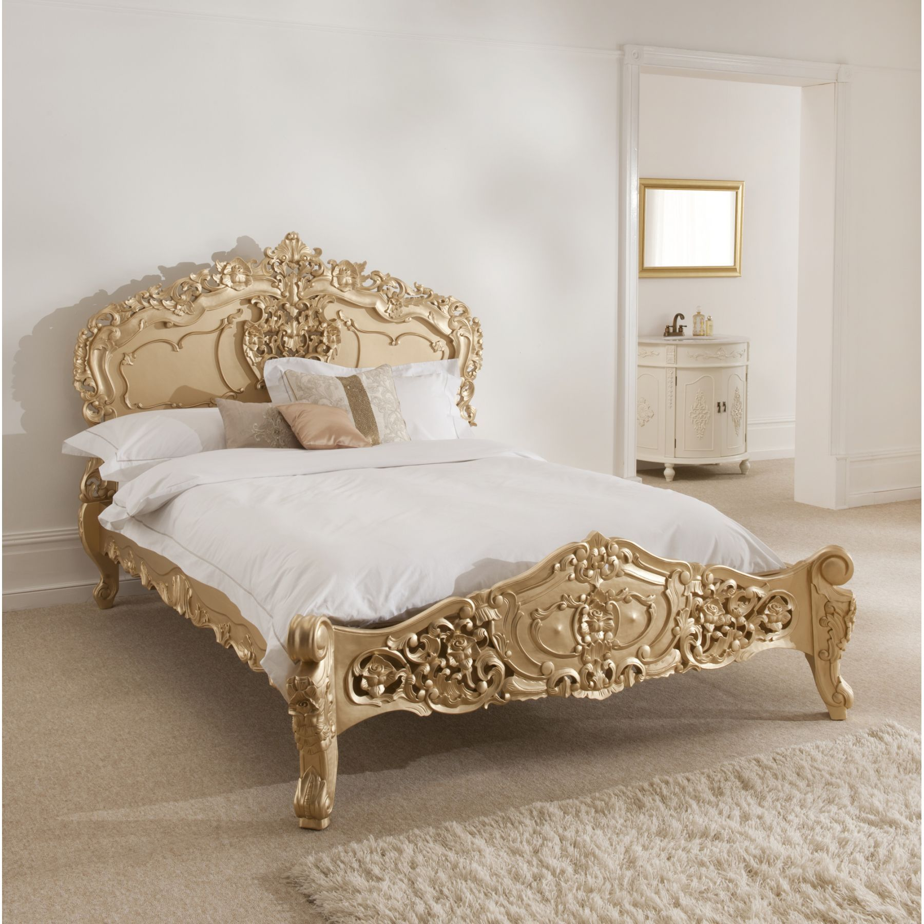 This Rococo style mahogany bed with an antique gold finish is