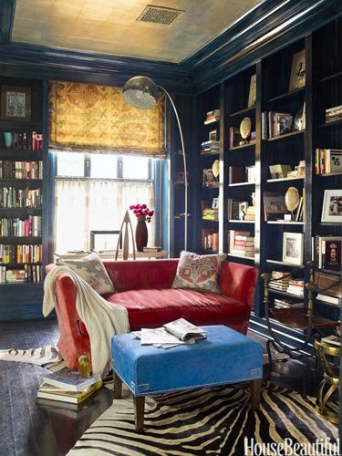 I love the cozy royal blue walls and the pop from the rosy couch.