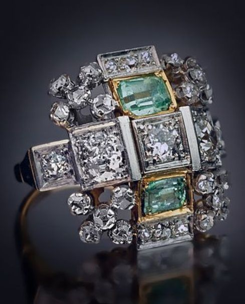 An Art Deco white and yellow gold, diamond and green beryl ring, circa 1935.  The geometric ring designed as a cross shaped stylised pyramid with a flat top, set with two emerald cut green beryls and old European cut diamonds, surrounded by four rose-cut diamond clusters, mounted in white and yellow gold. #ArtDeco #ring