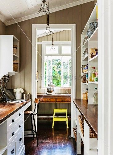 Schmale Küche im Landhausstil mit beidseitigem Einbau und Blick durch Durchgang auf Arbeitsplatz mit Sekretär und gelbem Hocker am Fenster
