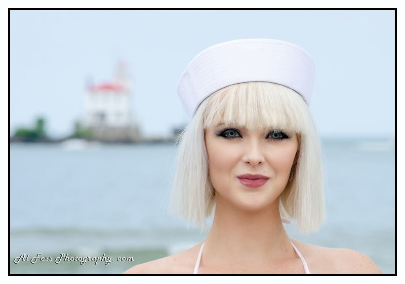 A woman in a sailor hat with the Fairport Harbor lighthouse in the background