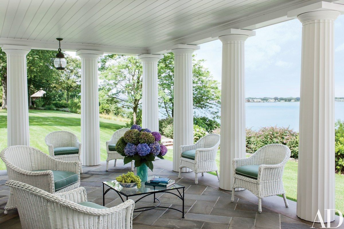 Doric columns frame a terrace furnished with vintage wicker; the view takes in Long Island's North Fork.