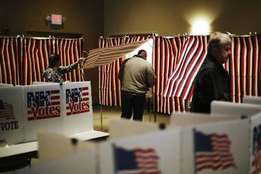 A voter steps into a voting booth to mark his ballot at a polling site for the…