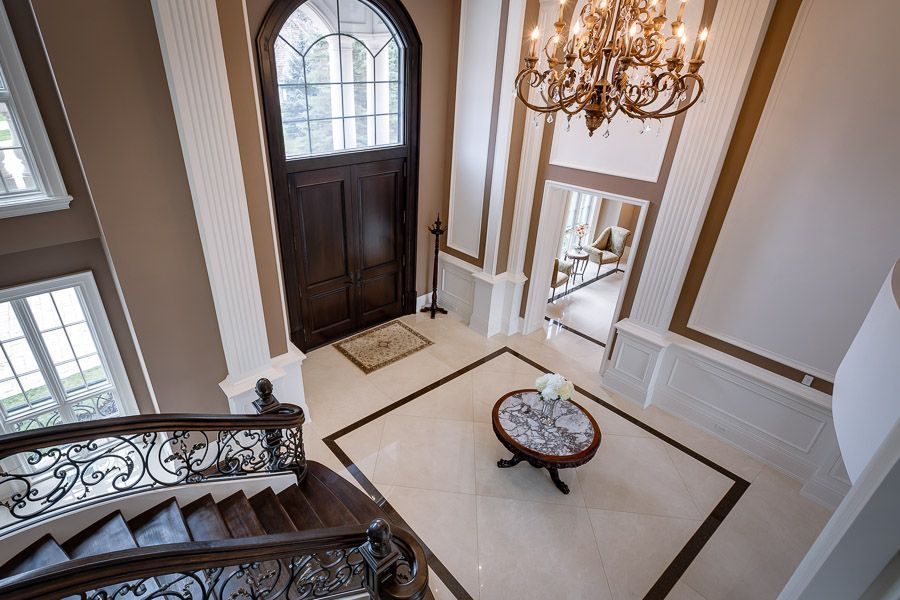 traditional entryway with limestone tile floors chandelier high ceiling wainscoting carpet