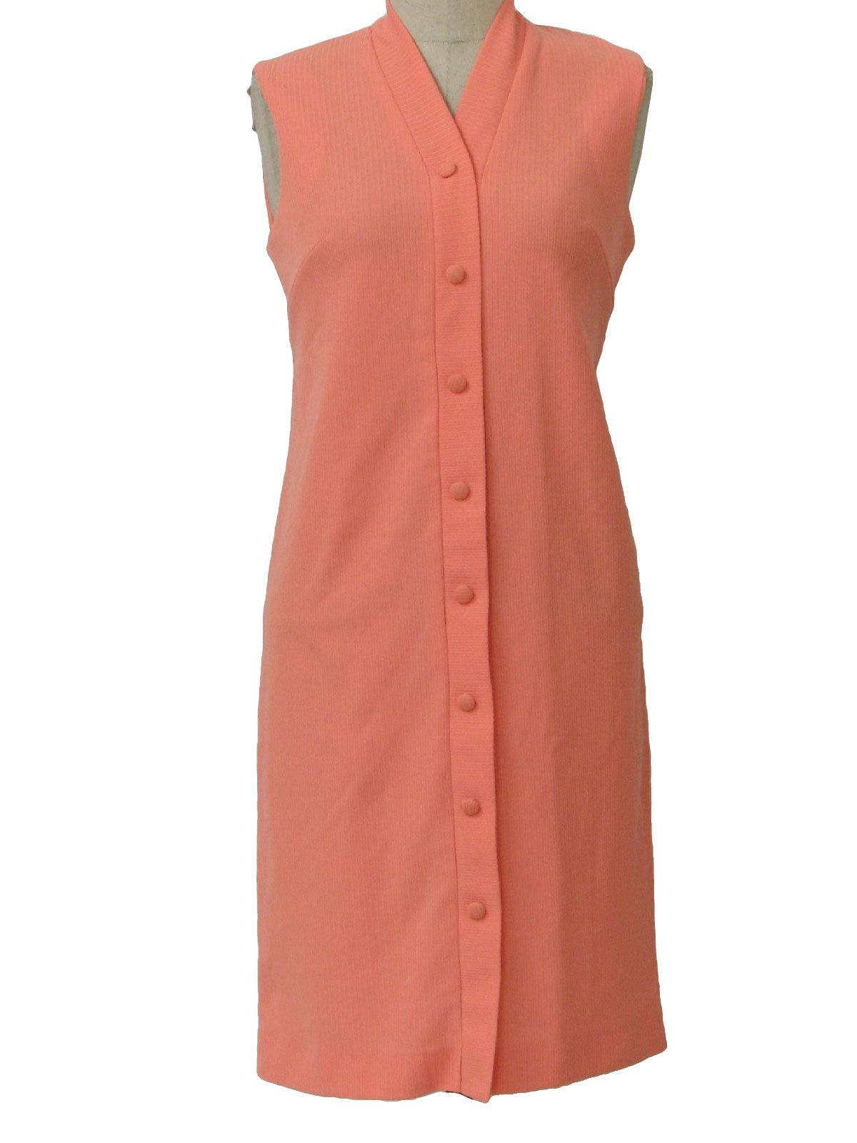 70s - peachsleeveless mid length shift style knit dress. A rib texture, with bust darts, faux front button placket with fabric covered accent buttons, a banded V-neck and back zip closure.