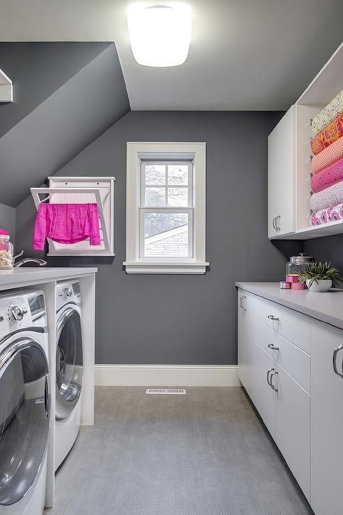 Pink and gray laundry room features walls painted charcoal gray lined with an enclosed washer and dryer next to a wall-mount drying rack alongside a gray tiled floor. #graylaundryrooms Pink and gray laundry room features walls painted charcoal gray lined with an enclosed washer and dryer next to a wall-mount drying rack alongside a gray tiled floor. #graylaundryrooms